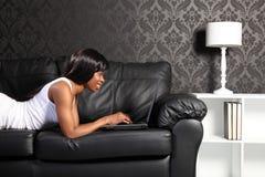 Mulher bonita do americano africano em casa com PC imagem de stock royalty free