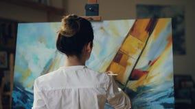 A mulher bonita do artista especializado está pintando ondas e barco do mar do seascape com pinturas acrílicas na paleta da terra video estoque