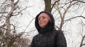 A mulher bonita do close-up monta um balanço e sorrisos no inverno na floresta filme