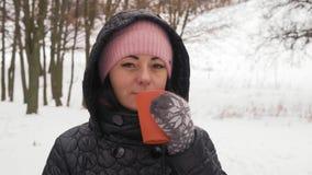 Mulher bonita do close-up no café quente das bebidas cor-de-rosa do chapéu no inverno na floresta filme