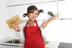 Mulher bonita do cozinheiro confundida e expressão frustrada da cara que veste o avental vermelho que pede a ajuda que guarda o p Imagem de Stock Royalty Free