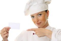 Mulher bonita do cozinheiro que prende o cartão em branco Imagem de Stock