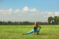 Mulher bonita do esporte que faz esticando o exercício da aptidão no parque da cidade na grama verde Fotos de Stock Royalty Free