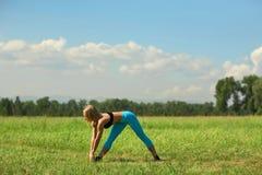 Mulher bonita do esporte que faz esticando o exercício da aptidão no parque da cidade na grama verde Fotos de Stock