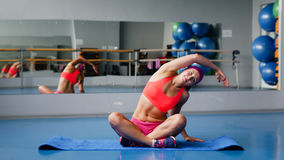 Mulher bonita do esporte que faz esticando o exercício da aptidão na ginástica do esporte yoga Imagens de Stock