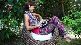 Mulher bonita do freelancer que trabalha em um computador em sua casa de campo com o jardim tropical verde Console de Bali, Indon filme