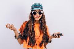 A mulher bonita do moderno novo nos óculos de sol que vestem no tampão e a música de escuta do t-shirt alaranjado nos fones de ou fotos de stock