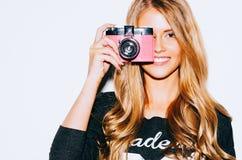 Mulher bonita do moderno que toma fotos com a câmera retro cor-de-rosa do filme no fundo branco Fim acima indoor Cor morna Fotografia de Stock Royalty Free