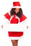 Mulher bonita do Natal no chapéu de Santa com placa branca vazia Fotos de Stock