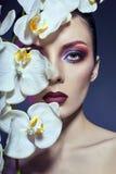 Mulher bonita do Nude com um ramo da orquídea branca em suas mãos, imagens de stock