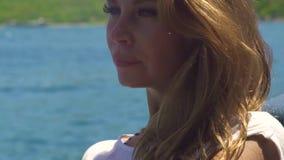 Mulher bonita do retrato com cabelo dourado longo no fundo azul do mar Feche acima da mulher atrativa da cara com cabelo marrom video estoque