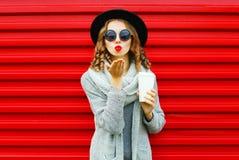 A mulher bonita do retrato da forma com copo de café funde os bordos vermelhos Imagens de Stock Royalty Free