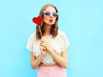 Mulher bonita do retrato e pirulito vermelho sobre o azul colorido Fotos de Stock