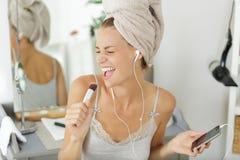 A mulher bonita do retrato que canta com compõe a escova fotos de stock royalty free