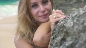 Mulher bonita do retrato que sorri e que olha à câmera na praia rochosa do mar Mulher feliz da cara com cabelo longo no verão filme