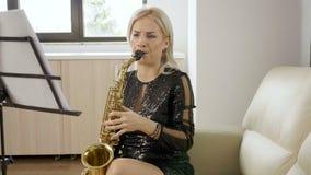 Mulher bonita do saxofonista que joga no saxofone na sala de visitas video estoque