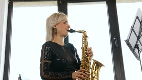 Mulher bonita do saxofonista que joga no saxofone na sala de visitas vídeos de arquivo
