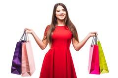 Mulher bonita do sorriso com os sacos shoping da cor nas mãos no fundo branco Fotografia de Stock Royalty Free