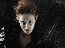 Mulher bonita do vampiro atrás do indicador chuvoso fotos de stock