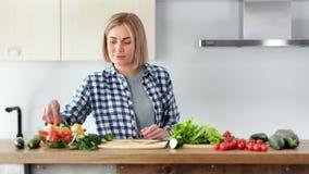 Mulher bonita do vegetariano que cozinha a salada fresca e que tenta os vegetais que olham o tiro médio da câmera filme
