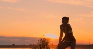 Mulher bonita do voleibol da recepção do saque no biquini na praia no por do sol filme