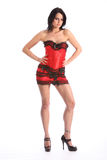 Mulher bonita dos pés longos 'sexy' na saia vermelha do espartilho Foto de Stock Royalty Free