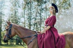 Mulher bonita e cavalo marrom fotografia de stock