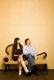 Mulher bonita e homem novo que sentam-se no sofá Imagens de Stock Royalty Free