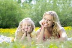 Mulher bonita e menina que jogam em uma tabuleta, na natureza, encontrando-se em uma cobertura na grama Foto de Stock