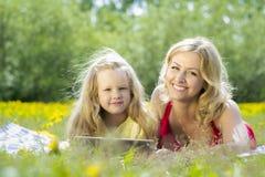 Mulher bonita e menina que jogam em uma tabuleta, na natureza, encontrando-se em uma cobertura na grama Imagens de Stock