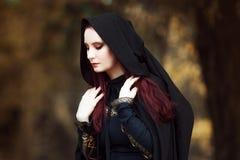 Mulher bonita e misteriosa nova nas madeiras, no casaco preto com capa, na imagem do duende da floresta ou na bruxa foto de stock royalty free