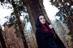 Mulher bonita e misteriosa nova nas madeiras, no casaco preto com capa, na imagem do duende da floresta ou na bruxa fotografia de stock royalty free