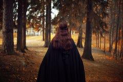 Mulher bonita e misteriosa nova nas madeiras, no casaco preto com capa, na imagem do duende da floresta ou na bruxa, traseira fotografia de stock royalty free