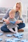 Mulher bonita e seu bebê que jogam com partes do enigma ao sentar-se em um tapete na sala de visitas Imagens de Stock Royalty Free