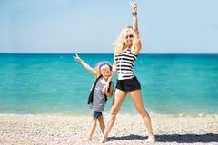 Mulher bonita e sua filha encantador que descansam na praia imagens de stock