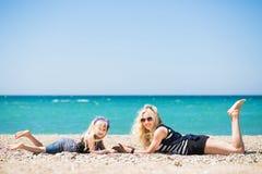 Mulher bonita e sua filha encantador que descansam na praia fotografia de stock