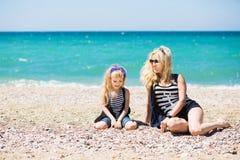 Mulher bonita e sua filha encantador que descansam na praia fotos de stock royalty free