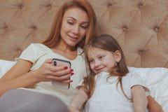 Mulher bonita e sua filha pequena que usa o telefone esperto imagens de stock royalty free