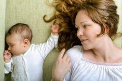 Mulher bonita e sua filha recém-nascida no sofá Imagens de Stock
