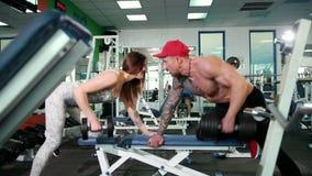 Mulher bonita e um homem brutal no peso de levantamento do gym Peso de levantamento da mulher lindo com seu marido no gym filme