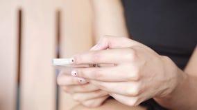 A mulher bonita elegante entrega texting no smartphone na cidade filme
