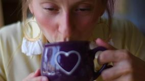 Mulher bonita em um café com uma xícara de café A jovem mulher atrativa está bebendo o cappuccino em um café vídeos de arquivo