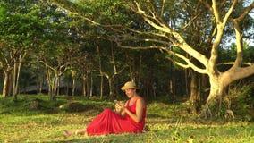 A mulher bonita em um chapéu de palha olha a informação no smartphone A mulher toma um selfie em uma clareira verde em Phu filme