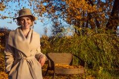Mulher bonita em um chapéu do revestimento e em um vestido branco para uma caminhada em um parque ou em uma floresta do outono Foto de Stock Royalty Free