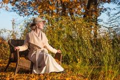 Mulher bonita em um chapéu do revestimento e em um vestido branco para uma caminhada em um parque ou em uma floresta do outono Imagens de Stock