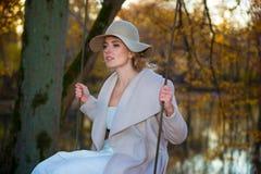 Mulher bonita em um chapéu do revestimento e em um vestido branco para uma caminhada em um parque ou em uma floresta do outono Fotos de Stock