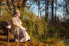 Mulher bonita em um chapéu do revestimento e em um vestido branco para uma caminhada em um parque ou em uma floresta do outono Imagem de Stock Royalty Free