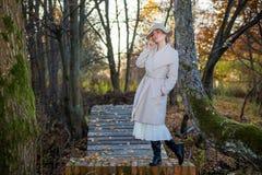 Mulher bonita em um chapéu do revestimento e em um vestido branco para uma caminhada em um parque ou em uma floresta do outono Imagem de Stock