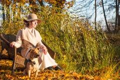 Mulher bonita em um chapéu do revestimento e em um vestido branco para uma caminhada em um parque ou em uma floresta do outono Fotografia de Stock Royalty Free