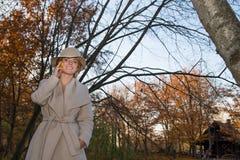 Mulher bonita em um chapéu do revestimento e em um vestido branco para uma caminhada em um parque ou em uma floresta do outono Imagens de Stock Royalty Free